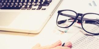 trading plan concept eyeglasses on balance sheet hand holding a pen
