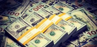 US dollar bills piled alongside each other