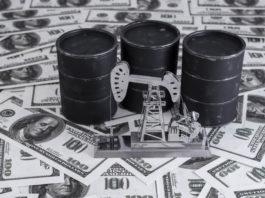 miniature oil barrels on top of dollar bills